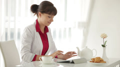 Beautiful woman sitting at table with cup of tea and using tablet Stock Footage