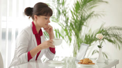 Charming girl sitting at table drinking tea and using tablet Stock Footage