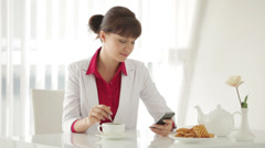 Beautiful young woman sitting at table with cup of tea and using cellphone Stock Footage