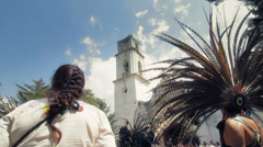 Aztec dancers gathered in front of church Stock Footage