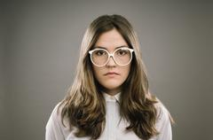 retro geek girl wearing glasses grainy vintage portrait - stock photo