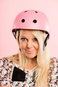 Stock Photo of funny woman wearing cycling helmet portrait pink background real people high
