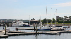 Boats docked in an active harbor, people walking, Maine Stock Footage