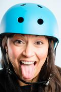 funny woman wearing cycling helmet portrait real people high definition blue  - stock photo