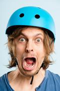 Funny man wearing cycling helmet portrait real people high definition blue ba Stock Photos