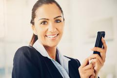 Closeup portrait of beautiful indian businesswoman sending text message using Stock Photos