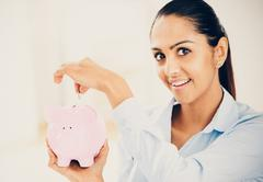 indian business woman saving money piggy bank - stock photo