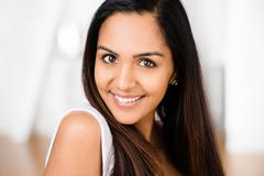closeup portrait of attractive indian young woman smiling - stock photo