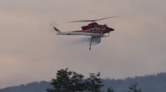 Helicopter, Bell 212 helicopter water drop at dusk, follow shot Stock Footage