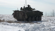 Stock Video Footage of military, LAV3 armoured fighting vehicle rolling through snow