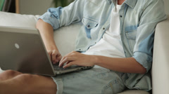 Young student sitting on sofa and using laptop Stock Footage