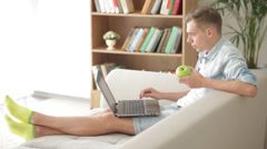 Student sitting on sofa using laptop and eating apple Stock Footage