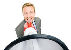 Happy young bussinessman shouting with megaphone on white background Stock Photos