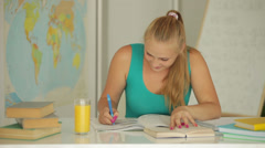 Beautiful girl sitting with book and writing in notebook Stock Footage