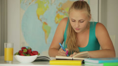 Attractive girl sitting at table and writing in notebook Stock Footage