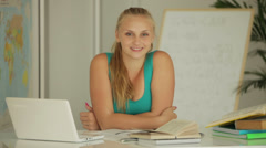 Attractive girl sitting at table with laptop and smiling Stock Footage