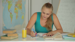 Charming girl writing in notebook and smiling Stock Footage