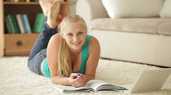 Happy girl relaxing on carpet with notebook Stock Footage