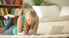 Cute girl lying on carpet using laptop and writing  in notebook Stock Footage