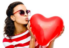Stock Photo of pretty mixed race girl holding red heart balloon