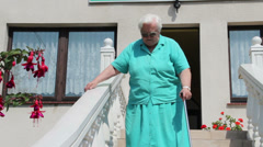 Old woman - problem with walking down stairs Stock Footage