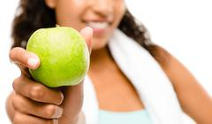 healthy young mixed race woman holding green apple isolated on white backgrou - stock photo