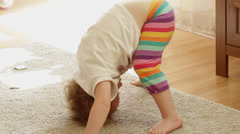 A cute little girl is bending over on floor HD Stock Footage