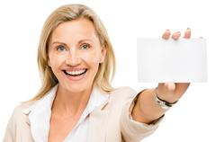 Mature business woman holding white placard smiling isolated on white backgro Stock Photos