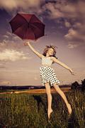 Jumping girl with umbrella Stock Photos