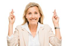 mature business woman holding fingers crossed isolated on white background - stock photo