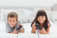 Stock Photo of Smiling siblings lying on bed playing video games together