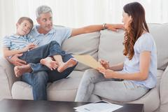 Stock Photo of Parents with their son sitting on sofa