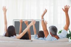 Family watching televison and rising theirs arms - stock photo