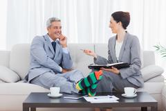 Funny businessman wearing stripey socks and laughing with his colleague - stock photo