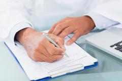 Hand of a doctor writing on a prescription - stock photo