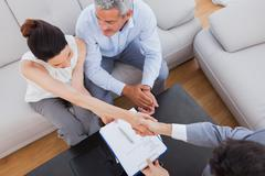 Businesswoman doing handshake with a businessman sitting on sofa - stock photo
