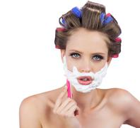 Delightful model in hair curlers posing with razor - stock photo