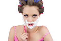 Serious model in hair curlers shaving her face - stock photo