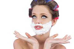 Stock Photo of Pensive woman posing with shaving foam on face