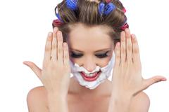 Stock Photo of Pensive woman with hands up and shaving foam on face