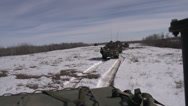 Stock Video Footage of military, LAV3 armoured fighting vehicle crossing open area follow