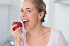 Woman munching apple - stock photo