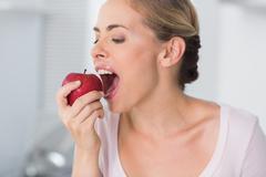 Pretty woman munching apple - stock photo