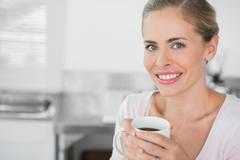 Stock Photo of Radiant blonde woman holding coffee