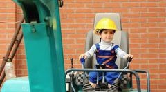Cute boy as a excavator operator controls the levers Stock Footage