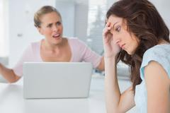 Unhappy woman thinking while her friend is interrogating her Stock Photos