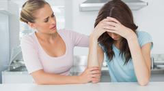 Stock Photo of Woman comforting her upset friend