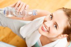 healthy young sportswoman drinking water at gym - stock photo