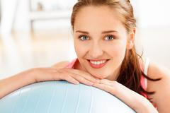 portrait of attractive young woman relaxing  fitness ball at gym - stock photo