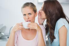 Stock Photo of Brunette telling secret to her friend while drinking coffee